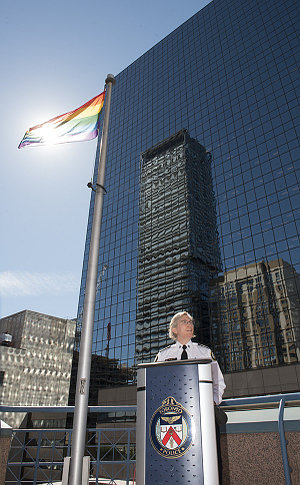 A woman in TPS uniform at a podium beside a rainbow flag