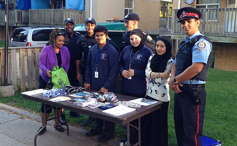 YIPI students and TPS uniformed officers in front of a house where they have set up a table with TPS materials and brochures.