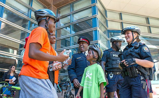 A man and woman in TPS uniform laugh alongside children in bike helmets