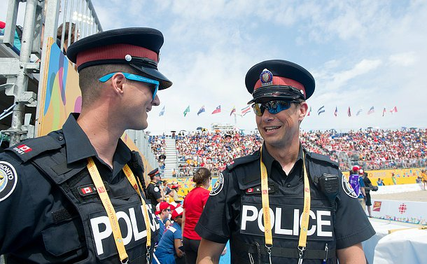 Two officers talking to each other on the sides of a beach volleyball court, the stands above them are filled with spectators.