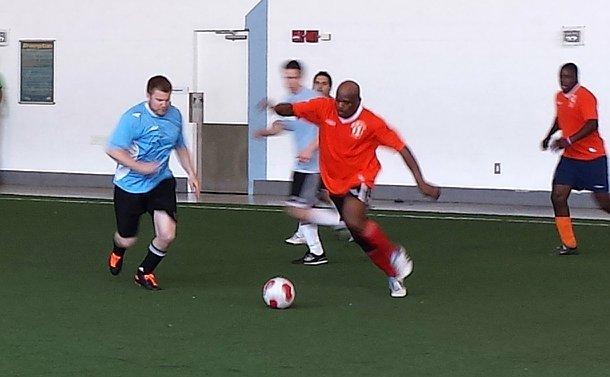 A man dribbles a soccer ball as an opposing team member runs toward him