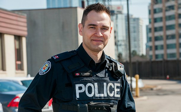 A male officer in uniform standing outdoors in a parking lot smiling into the camers