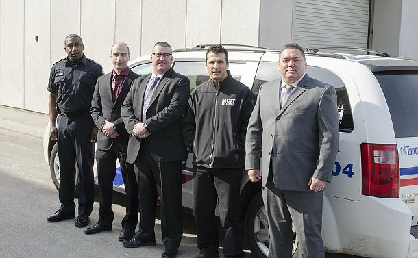 A group of men, one in TPS uniform standing against a mark TPS vehicle