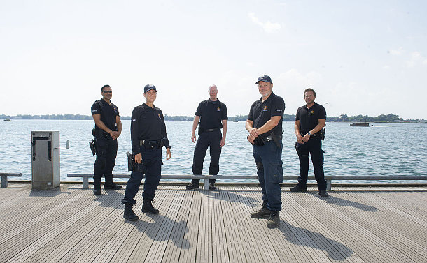 A group of people in TPS uniform on a lakefront boardwalk