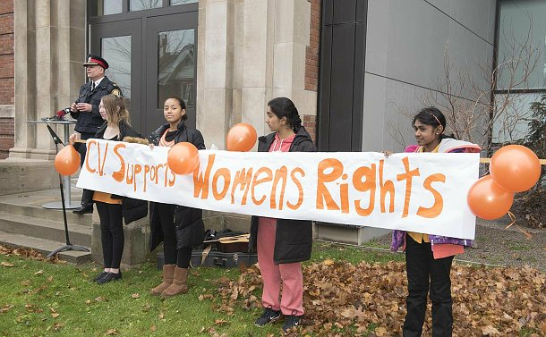 Girls holding a banner reading C.V. supports women's rights