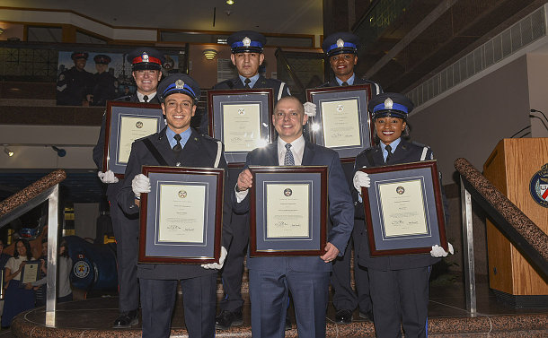 A group of Court and Police officers holding framed certificates