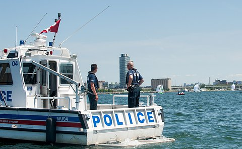 Two officers with their back turned to the camera on a police boat looking at a sailing race