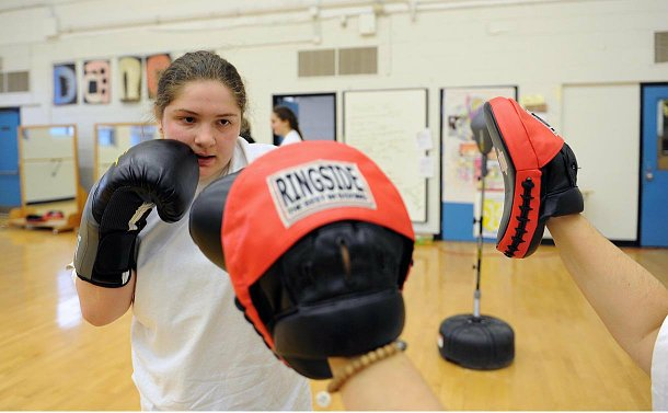 A girl with boxing gloves looking at outstretched arms with pads