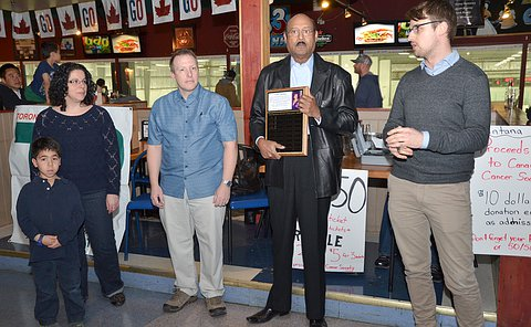 A group of people in a restaurant, one man speaking and holding a plaque