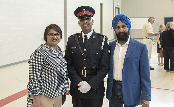 Man wearing a police uniform is flanked by another man and a woman