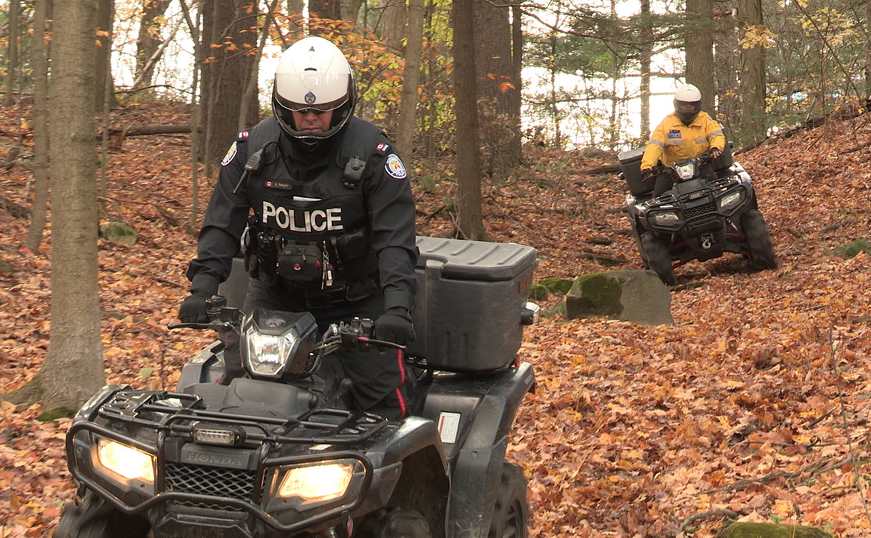 Two men in TPS uniform on all terrain vehicles in a forest