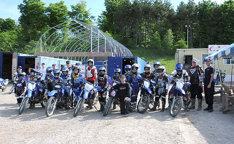 A large group of people wearing helmets and safety equipment on or beside dirt bikes