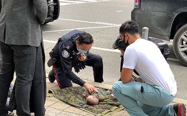 A police officer crouched over a baby on a sidewalk