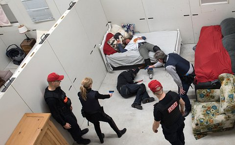 A fake violent scene with two people in police gear holding fake guns, pointed at a man holding a knife, a woman behind him is lying still on a bed.