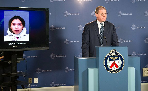 A man at a podium beside a photo of a woman on a TV