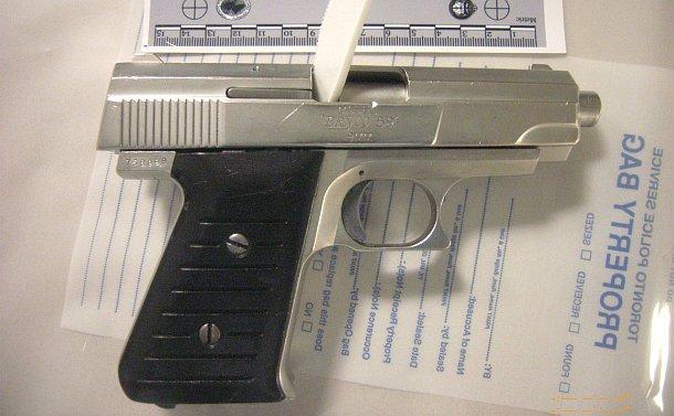 A handgun on a table beside a ruler