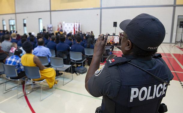 A woman in TPS uniform filming on her phone