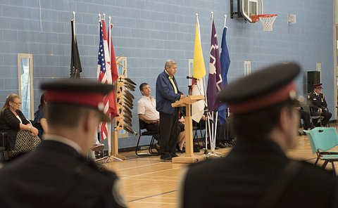 A man at a podium with two men in TPS uniform bowing heads in foreground