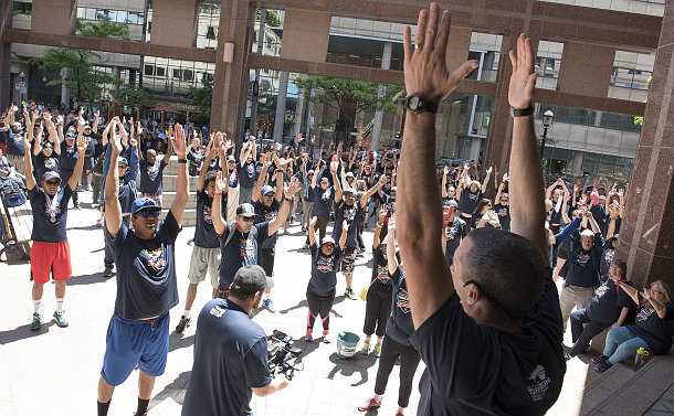 A group of people in matching t-shirts raising their hands in unison