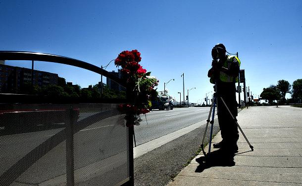 A person with radar gun in silhouette near flowers