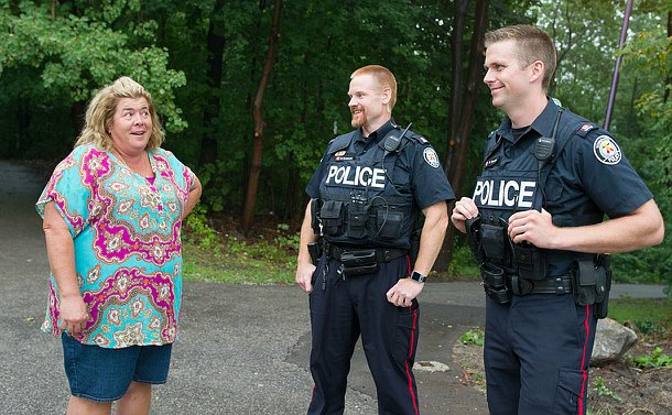 Two officers smiling and speaking to a woman outside a trail leading to a park