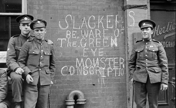 Three soldiers beside a buildng with graffiti