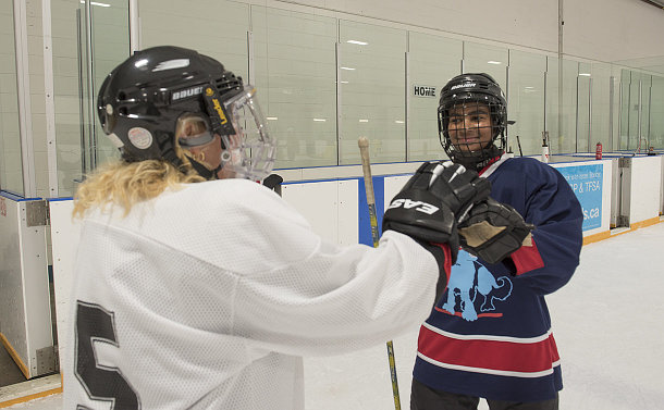 A boy fist bumps a woman both wearing hockey uniforms