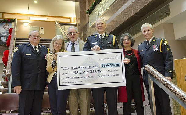 A group of people, three men in TPS uniform, holding an oversized cheque to United Way for $500,000
