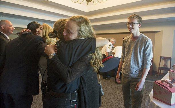 A teenage girl hugs a woman in TPS uniform as a teenage boy looks on. A woman hugs another man beside them