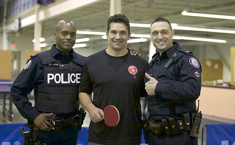 Two men in TPS uniform flank a man holding a table tennis paddle