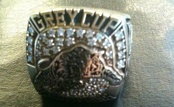 A close up of gold and diamond ring with a Hamilton Tiger-cats logo