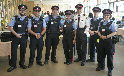A group of people in TPS auxiliary uniform with a man in TPS uniform