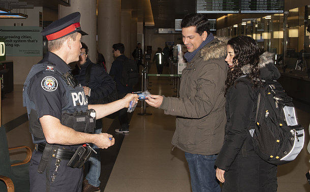 A man in TPS uniform handing out a flyer to another man