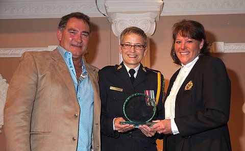 A woman in TPS uniform holding a glass award between a man and woman standing beside her