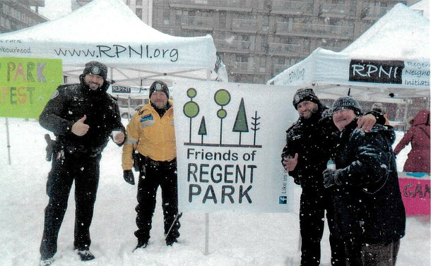 Men in TPS uniform with another man in front of a winterfest sign