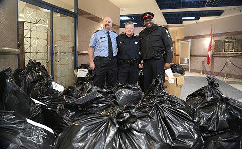 Three people in TPS uniform behind garbage bags