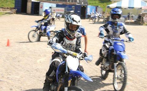 Several boys on dirt bikes turn a corner around a pylon