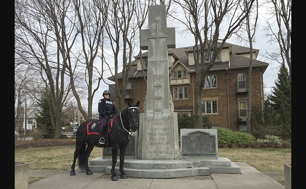 A woman in TPS uniform on a police horse beside a memorial marker