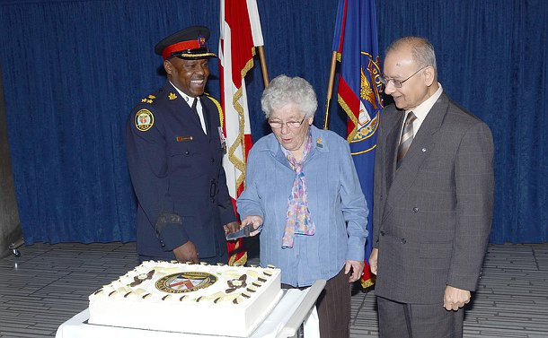 A woman cuts a cake with a TPSB logo on it as a man in TPS uniform and another man stand beside her