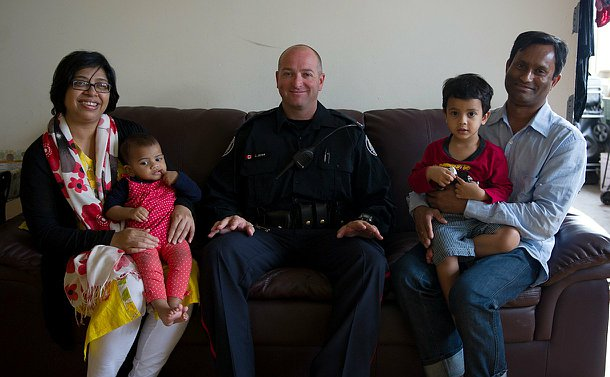 A man in uniform sits on a couch, on one side is a mother with a baby girl in her arms, on his other side, a father with his son in his lap.