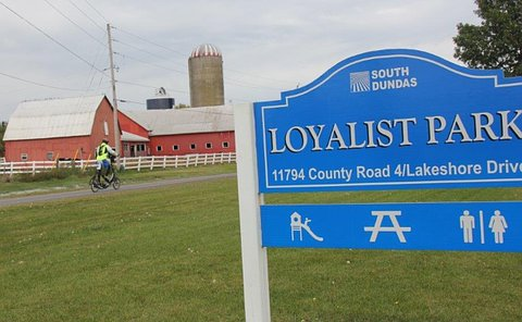 A sign stating Loyalist Park with a man on an elliptical bicycle passing a barn
