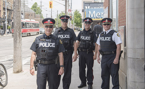 Four men in TPS uniform at a street corner