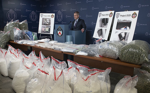 A man at a podium with tables with plastic bags with wrapped substances, some pill form, other dried marijuana