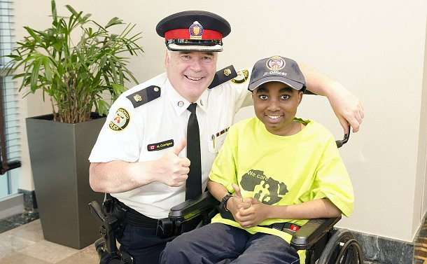 Man in a police uniform kneeling next to a boy in a wheelchair, both giving a thumbs-up