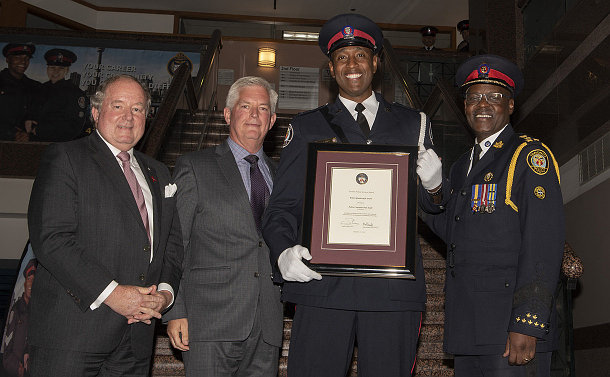 A group of people, a man in uniform holding framed certificate