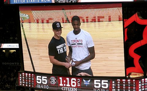 A photo of a jumbotron at a Raptors Game which shows a man receiving an award from another man on court