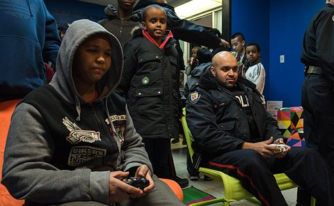A boy and a man in TPS uniform seated playing with video game controllers as other boys look on