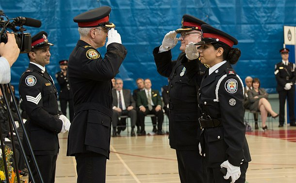 A woman and a man in uniform saluting, across them the deputy chief also in uniform