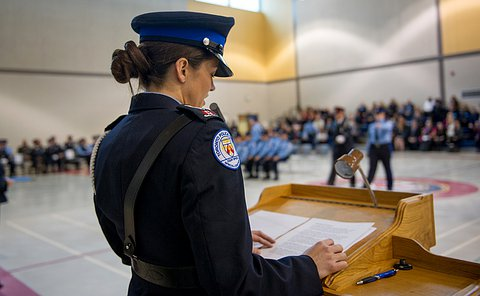 A woman in dress uniform with her back turned to the camera, standing at a podium looking down and reading off a paper.
