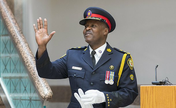 A man in TPS uniform waves